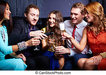 In the night club - Group of friends with flutes of...