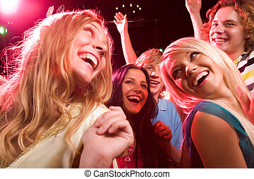 In the nightclub - Several smiling dancers having fun during...