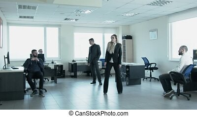 In the office, a man turns over a young woman. At work the blond businesswoman dances, the young man approaches to it and turns it as in dance.