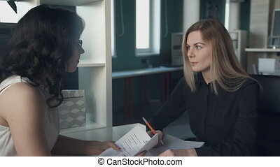 In the office, a young woman is interviewed in a female boss.