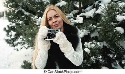 In the pine winter forest woman photographs and shows class.