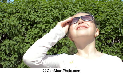 In the right part of the frame the girl looks at the sun dresses glasses drinks water from a plastic bottle