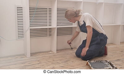 In the room blonde is kneeling and covers the floor brush...