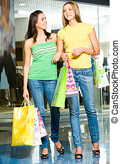 In the shopping mall - Image of two attractive women holding...