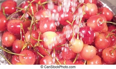 In the sink cherry in a colander under the water slow motion...