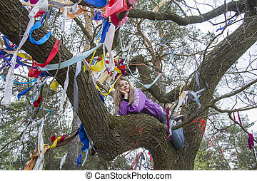 In the spring, a girl sits on a tree decorated with ribbons in the forest.
