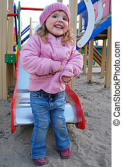 a little girl playing on the playground and laughs
