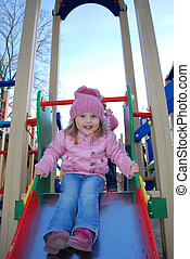 In the spring, a little girl playing on the playground, coming down from the hill and laughs