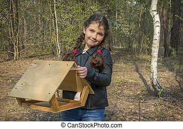 In the spring afternoon, in the forest, a girl is going to hang a feeder.