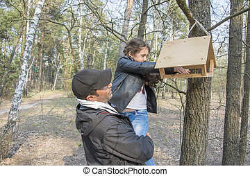 In the spring afternoon in the forest, dad and daughter put food in the bird feeder.