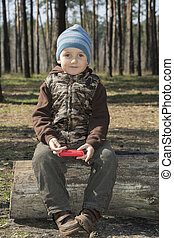 In the spring of a little boy sitting on a log in the forest.