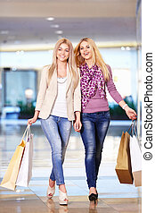 In the store - Beautiful girls with shopping bags walking in...