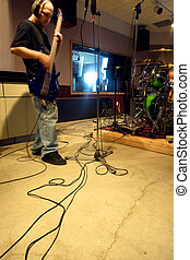 In the studio - A bass player recording his tracks in a ...