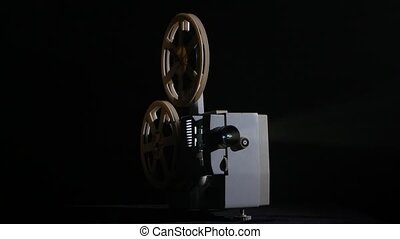 In the studio shows movie in a projector. Black background
