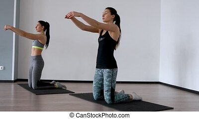 In the studio, two girls are engaged in pilates. Standing on their knees deviate back training the front of the thigh and spreading their arms out to the sides. 2 people synchronous execution