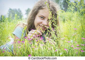 In the summer, a girl lies in a flower meadow.