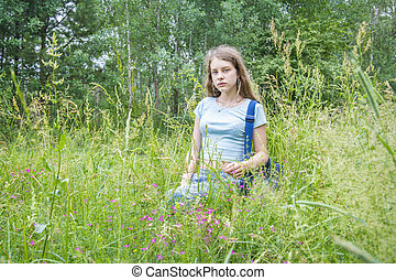 In the summer, a girl sits in a forest on a flower meadow.