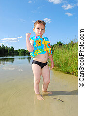 In the summer, bright sunny day, a beautiful boy stands in a lake, wearing swimming trunks and a vest.
