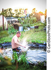 In the summer, bright sunny day, happy man jumping is bathed dives into the pond during sunset