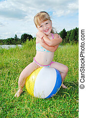 In the summer, bright sunny day, near the river, a little girl playing with a ball sitting on it.