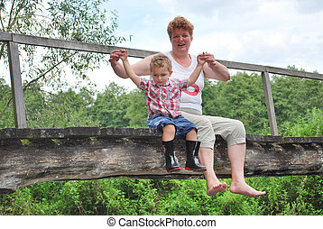 In the summer, bright sunny day, the grandmother with her grandson sitting with his legs dangling on the bridge