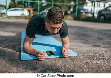 A man athlete performs an exercise on the mat.