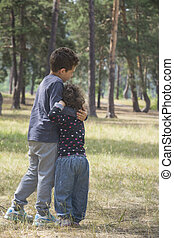 In the summer in the forest, the elder brother comforts his little sister.