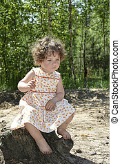 In the summer in the woods a little curly-haired girl sitting on a tree stump.