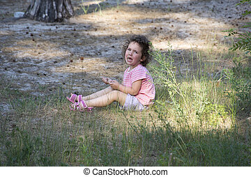 In the summer in the woods a little girl sits on the grass and cries heavily.