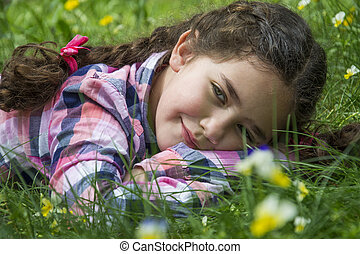 In the summer in the woods on the grass lies a little girl. She dreams about something.