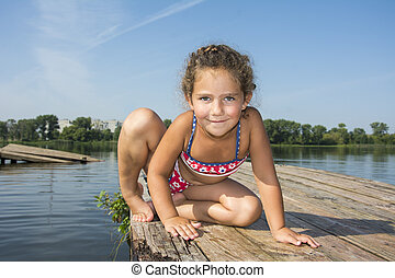 In the summer of bright sunny day on the pier sits a little girl in a bathing suit.