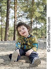 In the summer of funny little girl sitting on the ground in a pine forest.