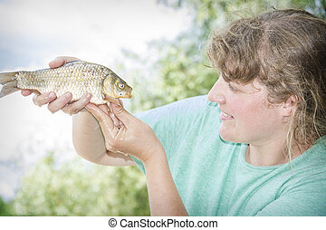 In the summer on a fishing curly girl caught a large carp...