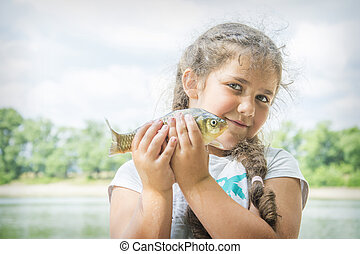 In the summer on a fishing little curly girl caught a large ...