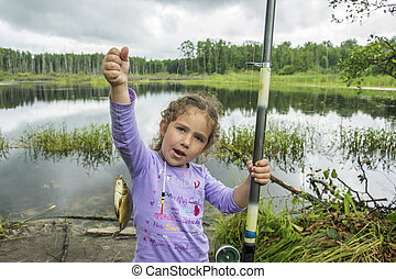 In the summer on a fishing little girl caught a large carp.
