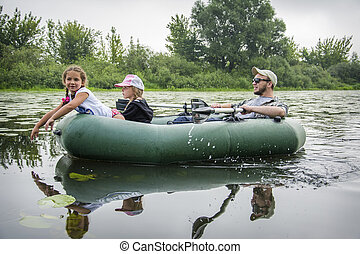 In the summer on a hot day in the inflatable rubber boat dad sails with daughters.