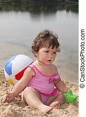 In the summer, on the beach in the sand little girl sits and plays with a bucket