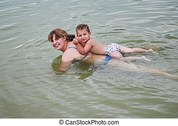 on the river, a boy with his mother floating in the water