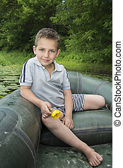 In the summer on the river a little boy sitting in a rubber boat and holding a water lily.