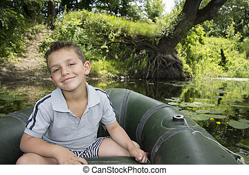 In the summer on the river a little boy sitting in a rubber boat near water lilies.