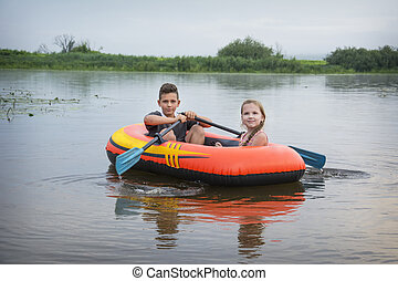 In the summer on the river happy boy with a girl swim in a rubber inflatable boat.