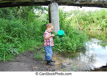 In the summer, outdoors, near the river and bridges, the little boy is playing with a ladle