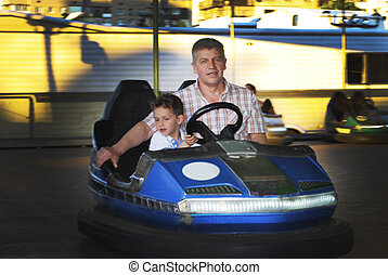 In the summer park rides on my grandfather with his grandson go by car.
