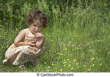In the summer sitting on a flower meadow curly pensive girl.