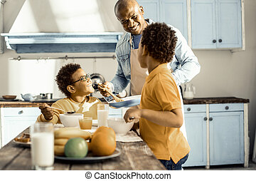 In the sun-drenched kitchen a man and his two sons eating and chatting.
