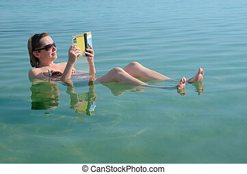 In the Waters of Dead Sea - Caucasian woman reads a book ...