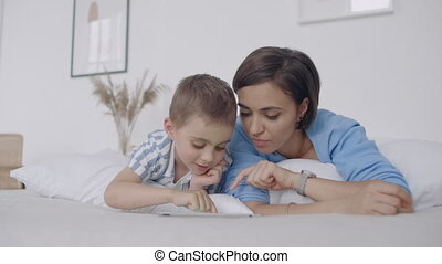 In the white bedroom, mom and son look at the tablet screen...