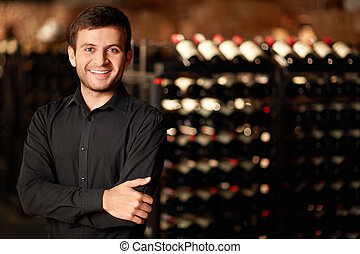 In the wine cellar - Sommelier of rack with bottles of wine