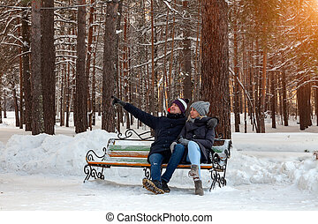 In the winter afternoon, a loving couple in jackets and hats are sitting on a bench in the woods in the snow hugging the guy shows his hand to the distance, the girl is holding a thermo mug of coffee.
