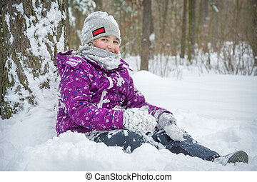 In the winter afternoon in a snowy forest, a girl sits in the snow under a tree.